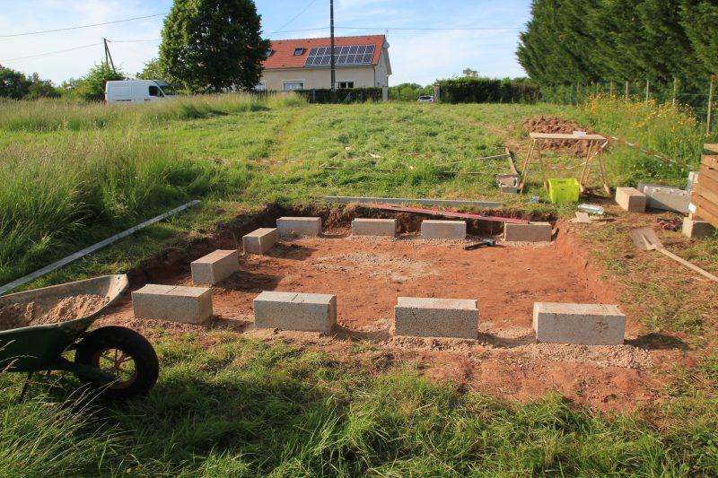 Mise en place des parpaings pour les fondations de l'abri de jardin